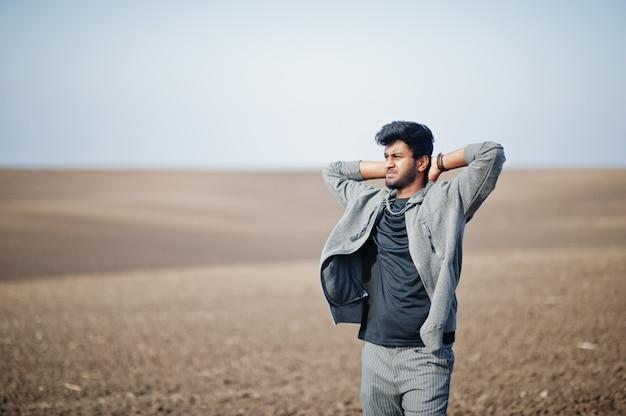 O homem indiano no vestuário desportivo levantou no campo sozinho.