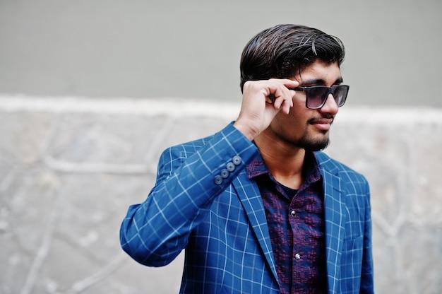 O homem indiano novo no terno azul e nos óculos de sol levantou ao ar livre.