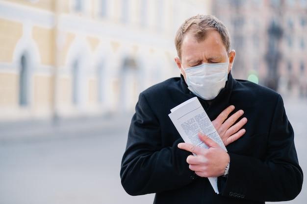 O homem infectado usa máscara médica, tem tosse constante, sintomas do covid-19, mantém enrolado jornal, posa na cidade ao ar livre, precisa de isolamento para parar de espalhar o coronavírus. medidas preventivas