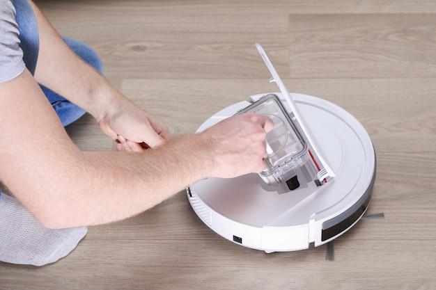 O homem insere um filtro e um recipiente para coletar poeira e resíduos em um aspirador de pó robô.