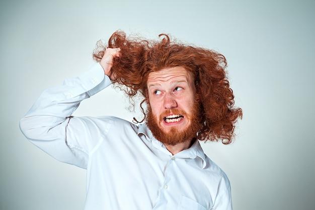 O homem irritado arrancando os cabelos