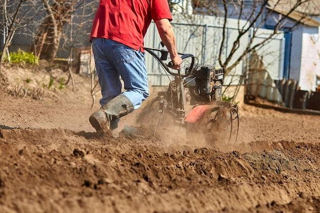 O homem jardineiro cultiva o solo do solo com um trator de cana ou rototiller, um cutivador, uma máquina de plantio