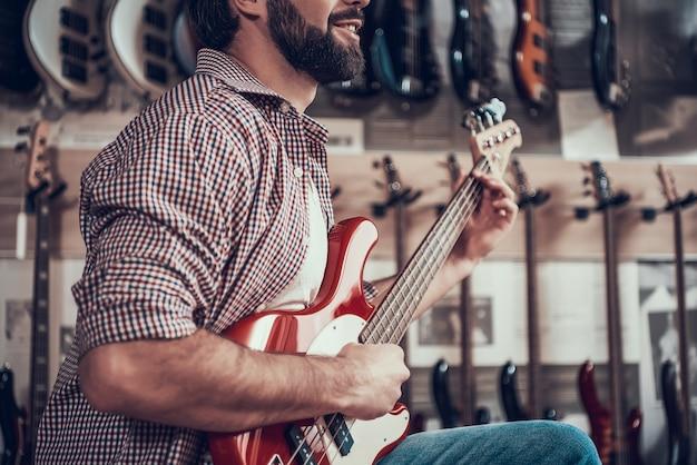 O homem joga na guitarra elétrica vermelha na loja do instrumento.