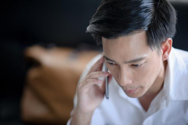 O homem joga o telefone, o smartphone da tela de toque do dedo, usa o telefone, datilografando sms, joga o jogo