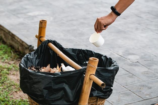 O homem jogando o copo de papel na lixeira ao ar livre. conceito de reciclagem em um dia ensolarado pela grama verde.