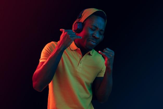 O homem jovem bonito feliz hippie ouvindo música com fones de ouvido no estúdio preto com luzes de néon. discoteca, boate, estilo hip hop, emoções positivas, expressão facial, conceito de dança Foto gratuita