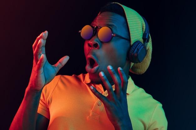 O homem jovem bonito feliz hippie ouvindo música com fones de ouvido no estúdio preto com luzes de néon. discoteca, boate, estilo hip hop, emoções positivas, expressão facial, conceito de dança