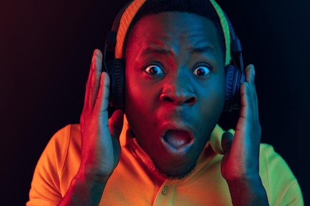 O homem jovem bonito feliz hipster ouvindo música com fones de ouvido no estúdio preto com luzes de néon. discoteca, boate, estilo hip hop, emoções positivas, expressão facial, conceito de dança