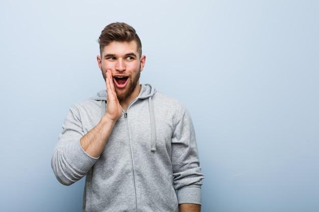 O homem jovem bonito fitness está dizendo uma notícia secreta sobre frenagem quente e olhando de lado