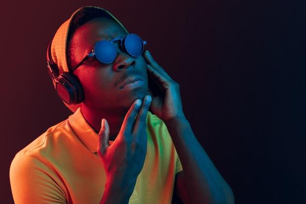 O homem jovem bonito sério triste hipster ouvindo música com fones de ouvido no estúdio preto com luzes de néon.
