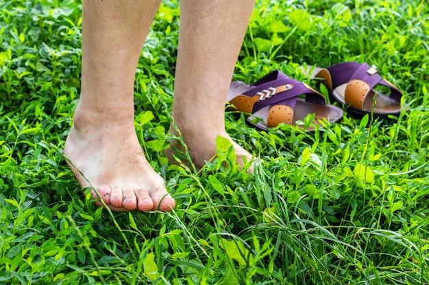 O homem largou os sapatos e caminhou na grama molhada