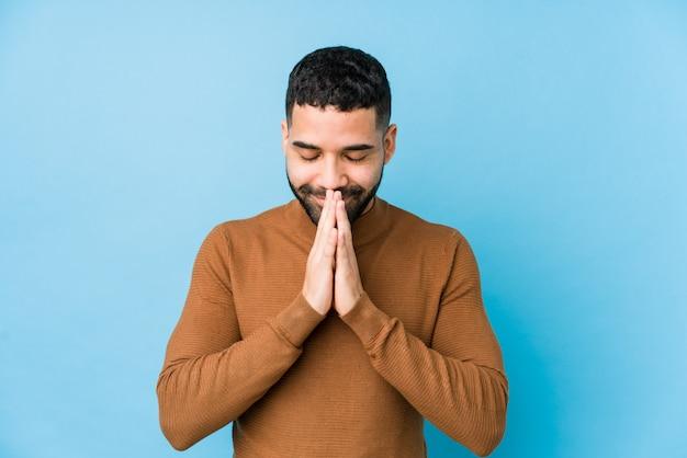 O homem latin novo contra uma parede azul isolada guardando as mãos reza dentro perto da boca, sente-se seguro.