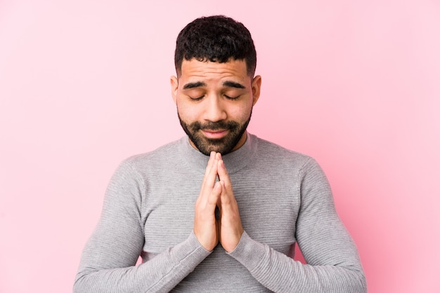 O homem latin novo contra uma parede cor-de-rosa isolada guardando as mãos reza dentro perto da boca, sente-se seguro.