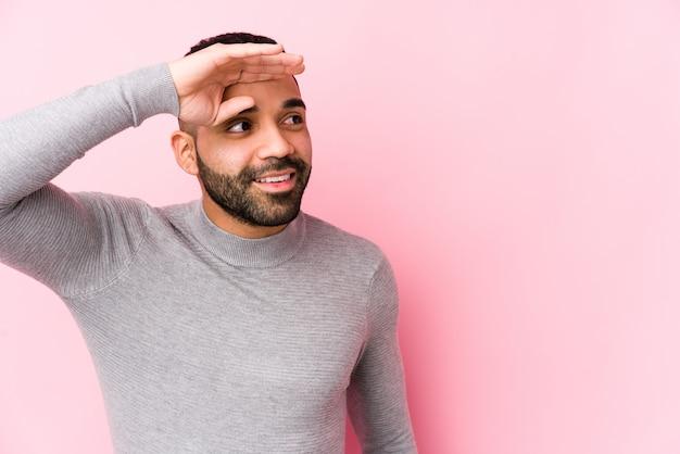 O homem latin novo contra uma parede cor-de-rosa isolou a vista longe mantendo a mão na testa.
