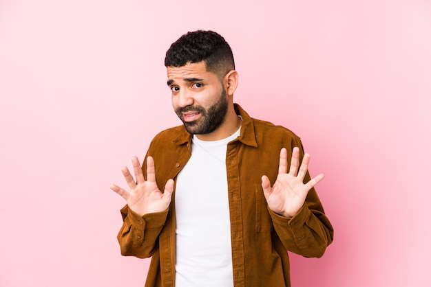 O homem latin novo contra uma parede cor-de-rosa isolou rejeitando alguém que mostra um gesto de nojo.