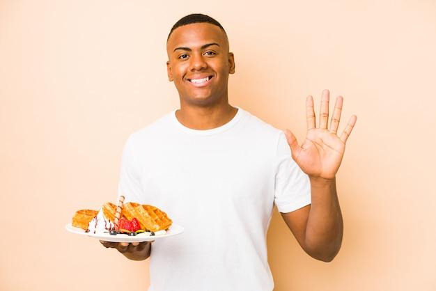 O homem latin novo que guarda um waffle isolou o número mostrando alegre de sorriso cinco com dedos.
