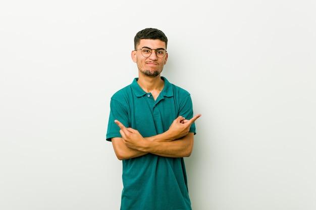 O homem latino-americano novo aponta lateralmente, está tentando escolher entre duas opções.