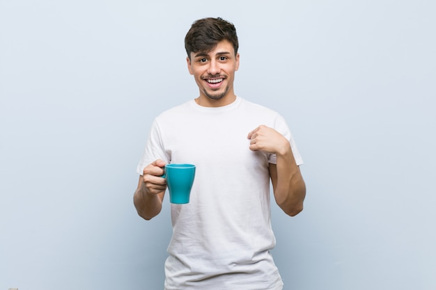 O homem latino-americano novo que guarda um copo surpreendeu apontar-se, sorrindo amplamente.