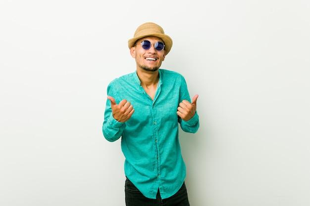 O homem latino-americano novo que veste um verão veste levantando ambos os polegares, sorrindo e confiante.