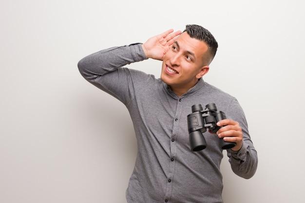 O homem latino tenta ouvir uma fofoca. ele está segurando um binóculo.