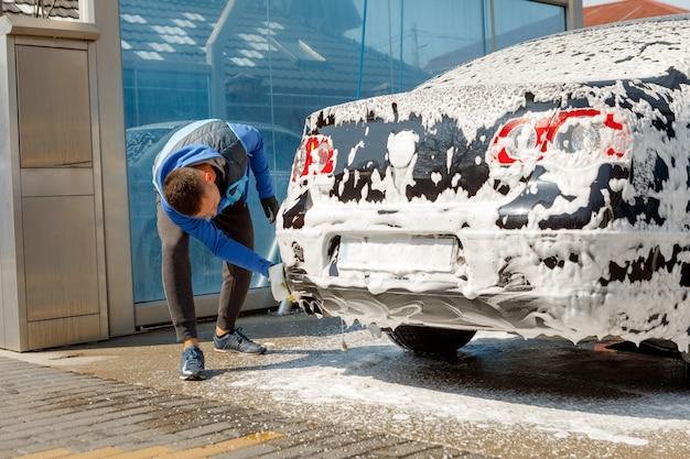 O homem lavando seu carro na lavagem de carros self-service. lava jato express