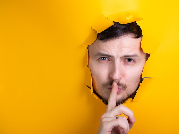 O homem leva o dedo indicador à boca por um orifício no papel amarelo. o homem diz para ficar em silêncio