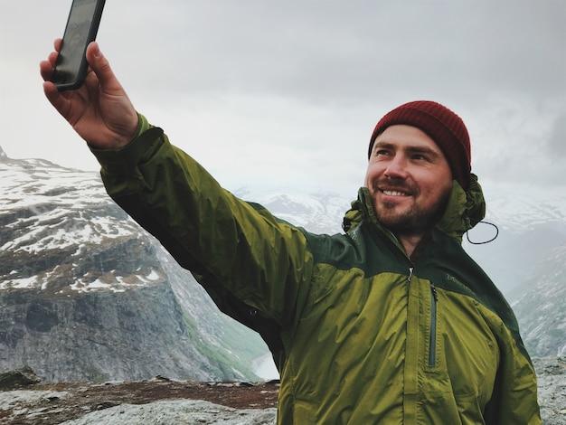 O homem leva um selfie na frente das montanhas