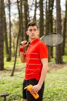 O homem levanta com uma raquete de tênis e um par termoelétrico alaranjado, no fundo do parque verde.