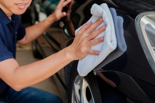 O homem limpa o carro.