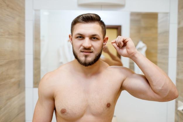 O homem limpa os ouvidos com cotonetes, procedimentos de higiene de rotina matinais. homem atlético no espelho do banheiro