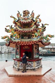O homem local de taiwan olha para a câmera enquanto queima joss paper dentro do santuário chinês na vila de pescadores de yehliu.