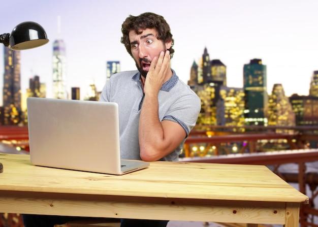 O homem louco novo em uma expressão de tabela surpreendido