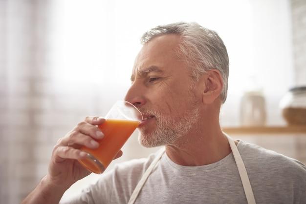 O homem maduro bebe o suco de laranja recentemente espremido.