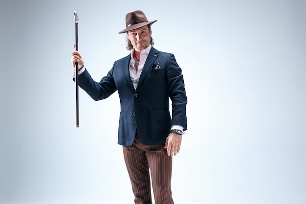 O homem maduro de terno e chapéu segurando a bengala.