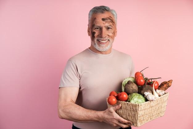 O homem mais velho continua útil com produtos caseiros cultivados em solo orgânico