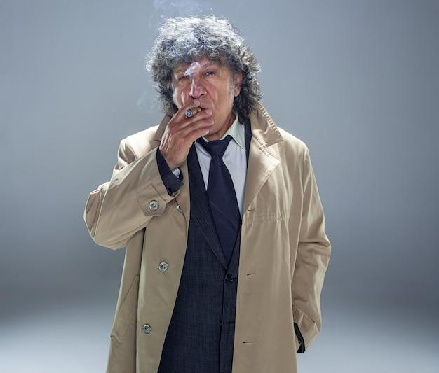 O homem mais velho de manto com charuto como detetive ou chefe da máfia.