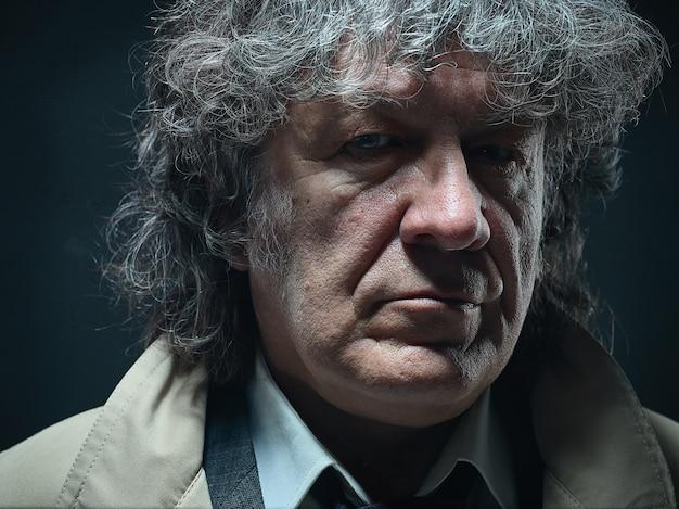 O homem mais velho vestido como detetive ou chefe da máfia.