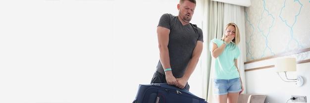 O homem mal consegue segurar a mala cheia ao lado da mulher
