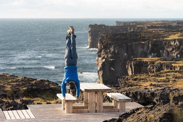 O homem mantém o equilíbrio em pé sobre as mãos na paisagem do mar com fundo de penhasco vertical perigoso, paisagem de nuvens durante o pôr do sol