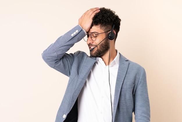 O homem marroquino do telemarketing trabalhando com um fone de ouvido isolado em um fundo bege percebeu algo e pretende a solução
