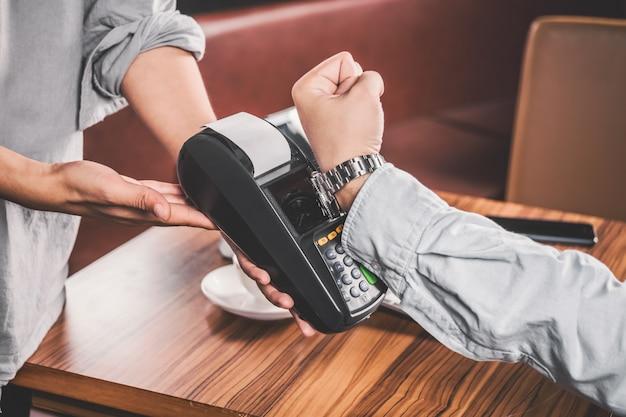 O homem moderno pagando com seu relógio