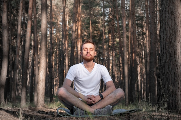 O homem moderno senta-se na floresta de pinheiros com os olhos fechados e desfruta do silêncio da natureza