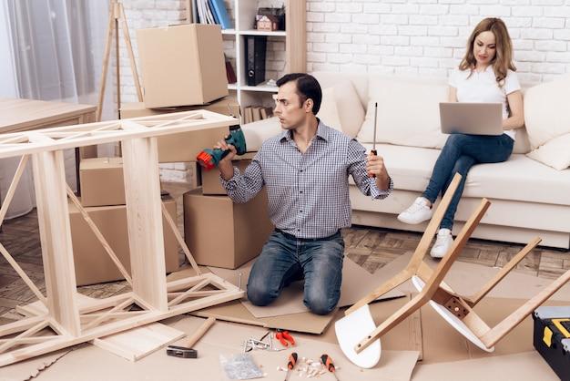 O homem monta a mobília dobra a mobília nova caixa para fora