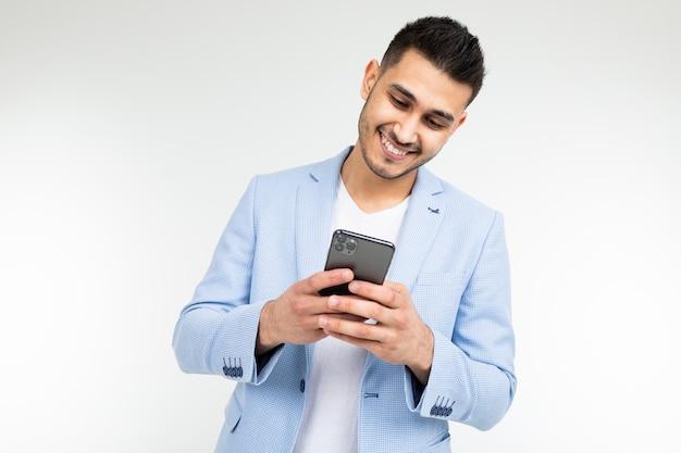 O homem moreno à moda em um casaco azul de sorriso olha o telefone em um branco