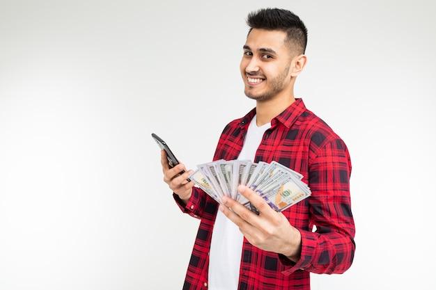 O homem moreno adorável alegre ganhou na loteria e recebeu um prêmio em dinheiro em um branco com espaço da cópia