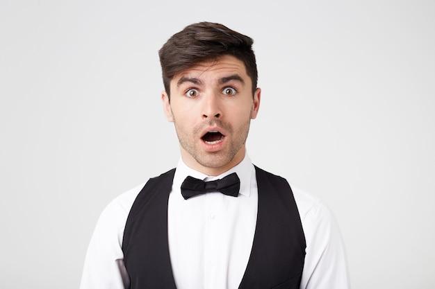 O homem moreno, elegantemente vestido com uma camisa branca, colete, gravata borboleta preta, parece chocado