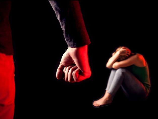 O homem mostra o punho na frente da mulher. pessoas, violência familiar, conceito de crime