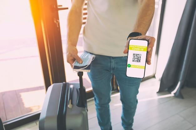 O homem mostrando o aplicativo passaporte de saúde digital no celular para viagens.