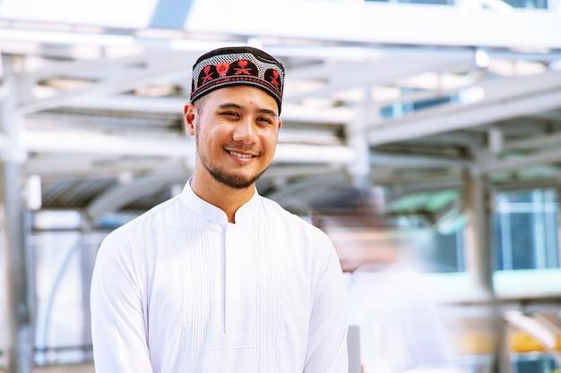 O homem muçulmano está de pé na cidade. ele está sorrindo.