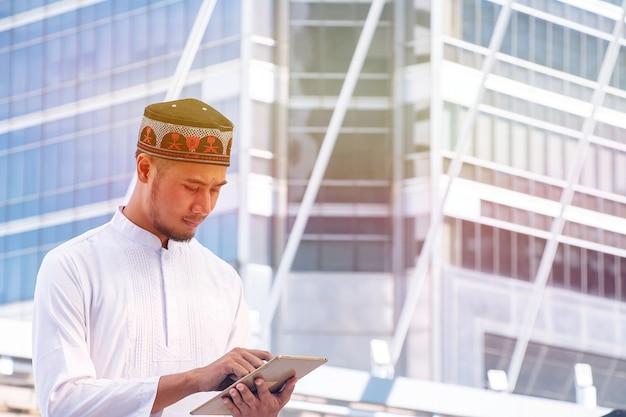 O homem muçulmano está olhando para tablet.